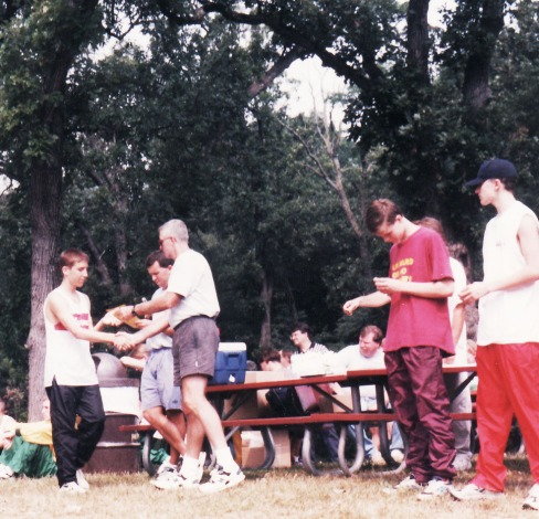 "Here is me accepting an award at the Crystal Lake South cross country meet as a junior in high school. I believe I came in 17th place out of perhaps 120 runners. I was always a ""mudder"" and a hill runner. On a rainy day I always performed a lot better, and for whatever reason I could grind out hilly courses and beat guys who would normally fly by me on flat terrain. Larry is dressed in the maroon running pants."