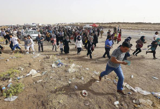 Refugees fleeing from Mosul head to the self-ruled northern Kurdish region in Irbil, Iraq, north of Baghdad, June 12, 2014. (Associated Press)